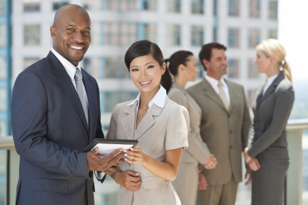 African American businessman and Chinese Asian businesswoman using tablet computer or touchpad with interracial group of business men & women team. Stock Photo - 19525312