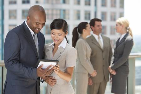 Afro-Amerikaanse zakenman en Chinese Aziatische zakenvrouw met behulp van tablet pc of iPad met interraciale groep van zakenlui en vrouwenteam.