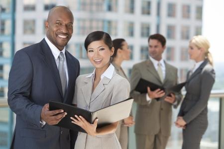 business case: Afro-Amerikaanse zakenman en Chinese Aziatische zakenvrouw met een zwarte map met interraciale groep van zakenlui en vrouwenteam. Stockfoto