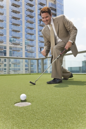Successful businessman  or man in a suit playing golf on a corporate putting green on roof of a skyscraper office building photo
