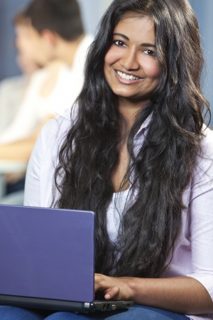 Indian Asian female student using laptop computer at college photo
