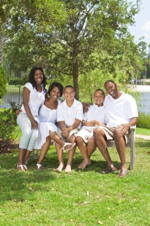 family one: Un felice nero African American famiglia di due genitori e tre figli, due ragazzi una ragazza, seduta insieme al di fuori.