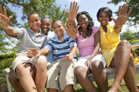 afroamericanas: Una familia afroamericano negro feliz de dos padres y tres hijos, dos ni�os, una ni�a sentados juntos fuera saludando divertirse.