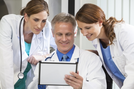 doctor tablet: Male & female medical doctors medical team using tablet computer in a hospital office