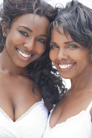 Een gelukkige African American vrouw en meisje, moeder en dochter, familie samen buiten in de zomer zon