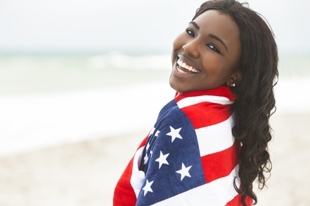 Beautiful happy smiling African American young woman or girl wrapped in American flag on a beach photo