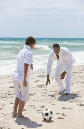 african american male: A happy African American man and boy, father and son, playing football soccer on a beach