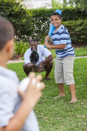 African American family, man, & boy children, father & two sons playing baseball together outside. photo