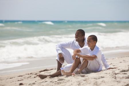 Een gelukkige African American man en jongen, vader en zoon, familie samen op een tropisch strand in de zomer zon