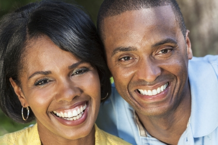 smiling teeth: A young African American woman & man couple outside in the summer Stock Photo