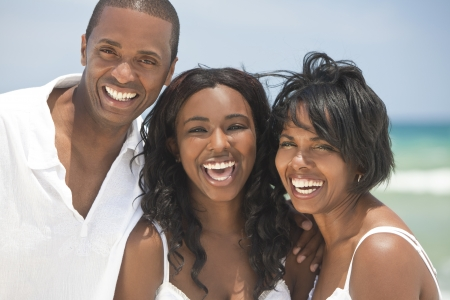african american male: A happy smiling laughing African American family of father mother & daughter at the beach in the summer