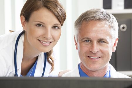 male and female: Male Female Hospital Doctors Using Computer Stock Photo