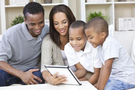 famille africaine: Africains famille, la m�re et le p�re parents et ses deux fils am�ricains, s'amuser en utilisant un ordinateur tablette ensemble � la maison