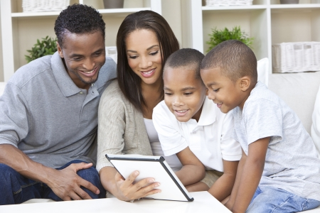 African American family, mother & father parents and two sons, having fun using a tablet computer together at home