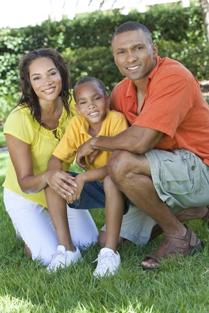 african family: A happy, smiling African American family, mother father & son, man woman & child, outside in summer sunshine.