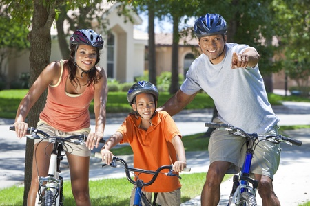 A young African American family, woman, man, father, mother & boy child riding bicycles in the summer photo
