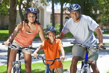 family health: A young African American family, woman, man, father, mother & boy child riding bicycles in the summer Stock Photo