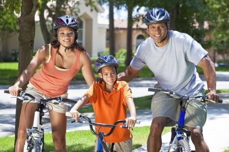Een jonge Afro-Amerikaanse familie, vrouw, man, vader, moeder en jongen kind fietsen in de zomer