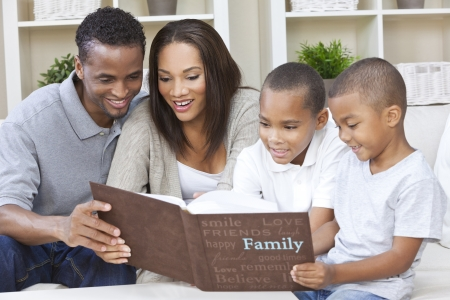 A happy African American man, woman and two boys, father, mother and sons, family sitting together at home looking at photo album photo
