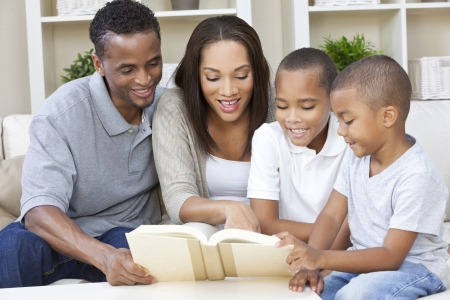 A happy African American man, woman and boys, father, mother and two sons, family sitting together at home reading a book Banco de Imagens