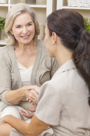 saleswoman: A saleswoman with shaking hands with a senior woman at home