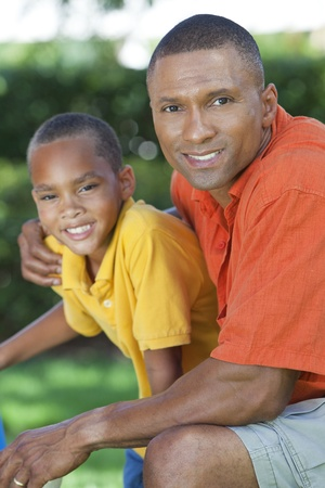 A happy African American man and boy, father and son, family together outside in summer sunshine Stock Photo - 19608597