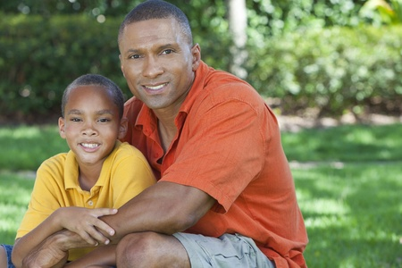 A happy African American man and boy, father and son, family together outside in summer sunshine Stock Photo - 19608588