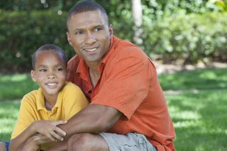 A happy African American man and boy, father and son, family together outside in summer sunshine Stock Photo - 19608598