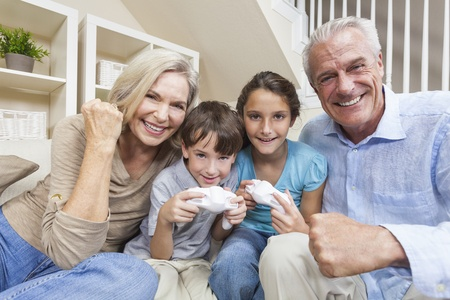 grandaughter: Happy family, senior adults   children, grandparents, grandson and grandaughter, having fun playing video console games together  Stock Photo