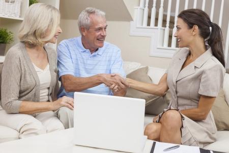 pareja en casa: Una vendedora con el ordenador port�til estrechando la mano de una pareja de ancianos en el hogar Foto de archivo
