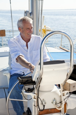 A happy senior man smiling sitting at the wheel of a sail boat on a calm blue sea photo