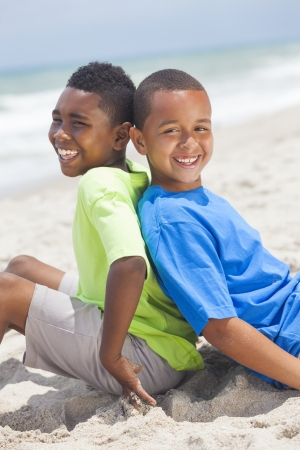 african family: Two young African American boys sitting back to back playing having fun on a sunny beach