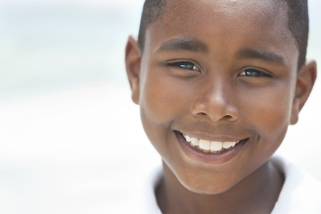 A happy smiling young African American boy at the beach in the summer photo