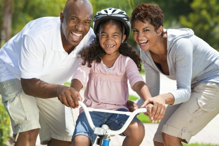 A young African American family with girl child riding her bicycle and her happy excited parents giving encouragement beside her  photo