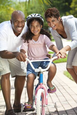 african family: A young African American family with girl child riding her bicycle and her happy excited parents giving encouragement beside her  Stock Photo