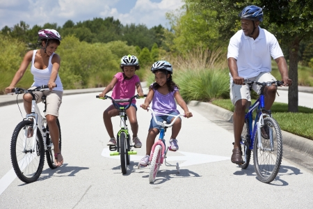 A Black African American family of two parents and two children, two girls, cycling together