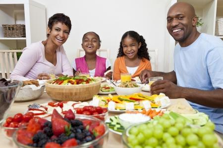 comida sana: Un atractivo feliz afroamericano, sonriendo familia de la madre, padre, dos hijas comen ensaladas y alimentos saludables en una mesa de comedor