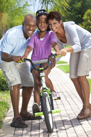 A young African American family with girl child riding her bicycle and her happy excited parents giving encouragement beside her  Stock Photo - 19608554