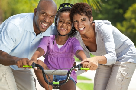 A young African American family with girl child riding her bicycle and her happy excited parents giving encouragement beside her  Banco de Imagens