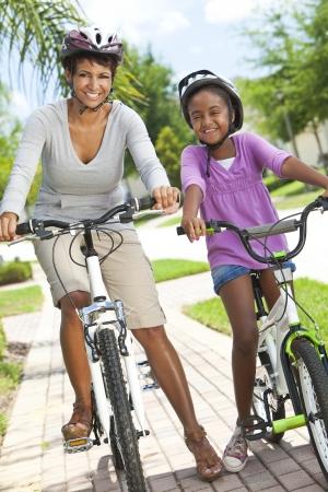 Een gelukkige African American vrouw en kind, moeder dochter, samen fietsen