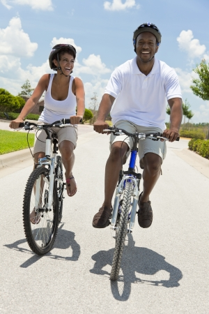 A Black African American adult man and woman couple cycling together