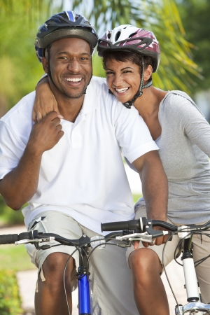 A happy laughing young African American couple with big smiles riding their bicycles outside photo