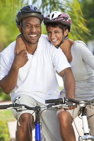 Een gelukkige lachende jong African American paar met grote glimlachen paardrijden hun fietsen buiten