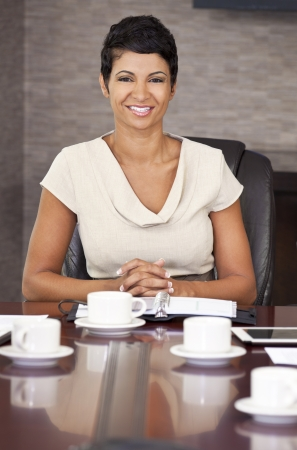 A happy African American woman, businesswoman, sitting   smiling at an office boardroom table  photo