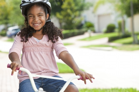 A pretty young African American girl with a big smile riding her bicycle outside