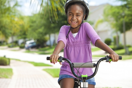 big smile: A pretty young African American girl with a big smile riding her bicycle outside