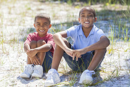 Two young African American boy children sitting together in the summer sunshine photo