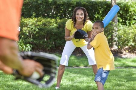 Afro-Amerikaanse familie, man, vrouw, jongen kind, moeder, vader, zoon spelen honkbal samen buiten. Stockfoto