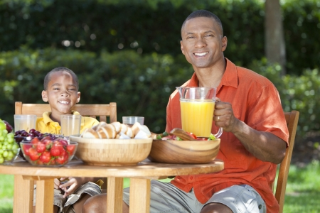 A happy, smiling African American father & son eating healthy food at a table outside, the father is serving a orange juice to the boy. Stock Photo - 19615005