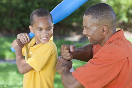 African American man & boy child, father and son playing baseball together outside.